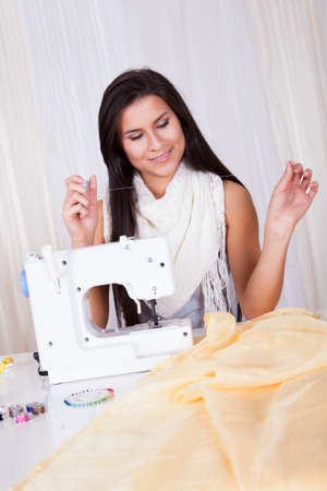 Smiling beautiful woman seated at a table with a length of fabric holding a reel of cotton threading her sewing machine Stock Photo - 16522400