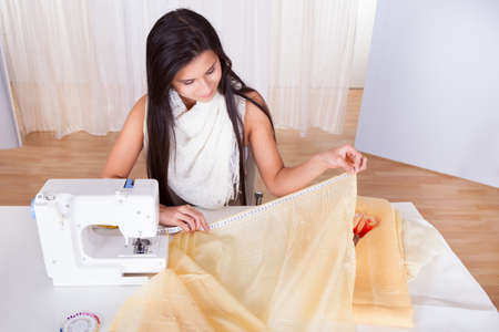Attractive stylish seamstress or interior designer measuring a length of neutral colored fabric alongside her sewing machine with copyspace Stock Photo - 16522108