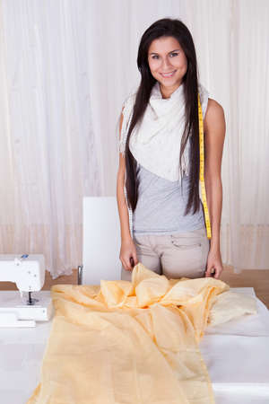 Attractive stylish seamstress or interior designer measuring a length of neutral colored fabric alongside her sewing machine with copyspace photo