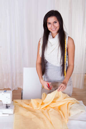 Beautiful woman with a measuring tape draped around her neck cutting fabric on a tabletop alongside her sewing machine photo
