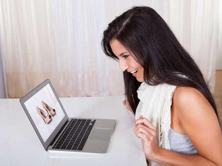 comprando zapatos: Mujer feliz sentado en su escritorio de compras en l�nea los cat�logos de navegaci�n ropa de color