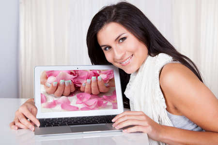 Happy woman looking for fingernail designs on her laptop at home Stock Photo - 16522098