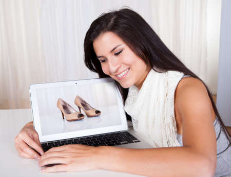 Woman shopping online for shoes finds a pair that she likes displayed on the screen of her laptop facing the camera photo