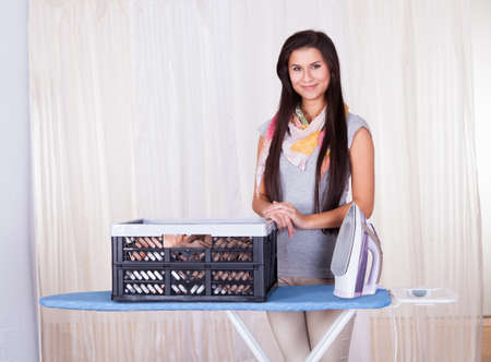 Cheerful beautiful housewife doing the ironing displaying a large container full of clean laundry Stock Photo - 16522259