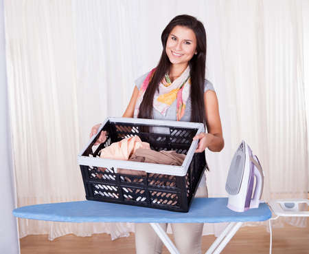 Cheerful beautiful housewife doing the ironing displaying a large container full of clean laundry photo