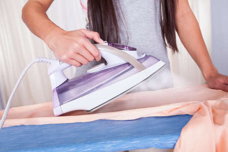 steam iron: Cheerful housewife with a beautiful smile standing at the ironing board ironing clothes against a white curtained window with copyspace Stock Photo
