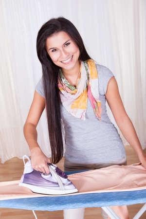 iron curtain: Cheerful housewife with a beautiful smile standing at the ironing board ironing clothes against a white curtained window with copyspace Stock Photo