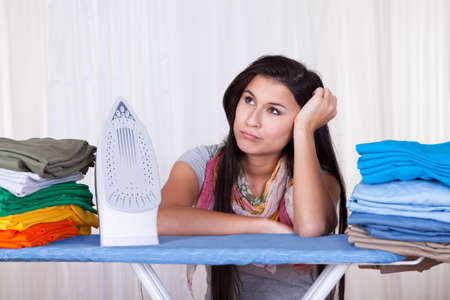 rueful: Fed up housewife sitting amongst her clean laundry piled on the ironing board daydreaming