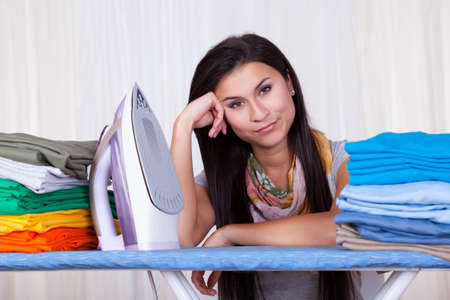 Fed up housewife sitting amongst her clean laundry piled on the ironing board daydreaming Stock Photo - 16522211