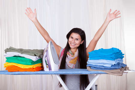Happy woman throws her arms in the air because she has finished and folded all of the ironing photo