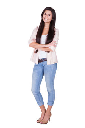 Full length isolated studio portrait of a trendy young woman in casual jeans and stilettos posing in a relaxed stance on white Stock Photo - 16522691