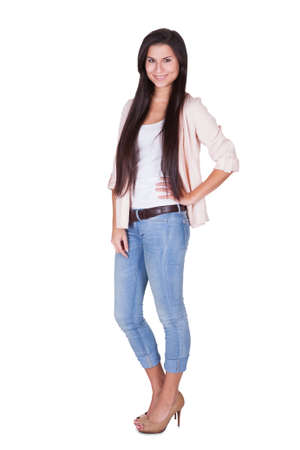 Full length isolated studio portrait of a trendy young woman in casual jeans and stilettos posing in a relaxed stance on white Stock Photo - 16522695
