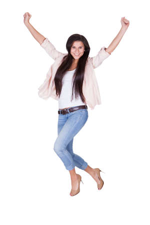 Full length portrait of a young shapely beautiful woman in trendy casual clothing waving her arms in the air isolated on white Stock Photo - 16522699