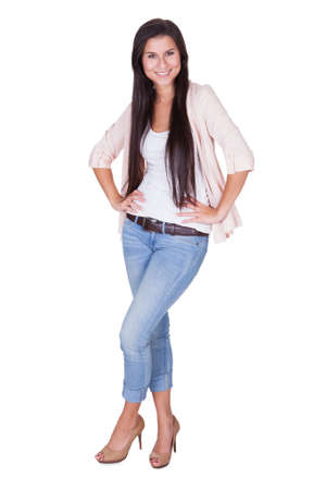 Full length isolated studio portrait of a trendy young woman in casual jeans and stilettos posing in a relaxed stance on white Stock Photo - 16522664