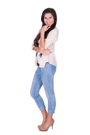 Full length isolated studio portrait of a trendy young woman in casual jeans and stilettos posing in a relaxed stance on white Stock Photo - 16522621