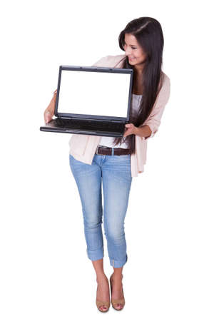 Beautiful charming woman holding a laptop facing the camera with a blank white screen for your text or advertising photo