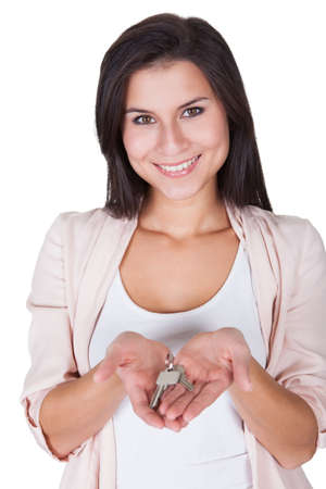 Attractive smiling woman holding up a set of keys belonging to her house or car in her hand isolated on white Stock Photo - 16522161