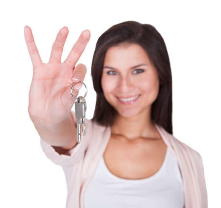 Attractive smiling woman holding up a set of keys belonging to her house or car in her hand isolated on white Stock Photo - 16522682