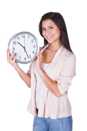 Beautiful woman holding a large round analog clock in her hands at chest height isolated on white Stock Photo - 16522156