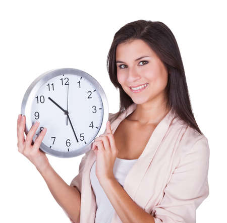 Beautiful woman holding a large round analog clock in her hands at chest height isolated on white Stock Photo - 16522644