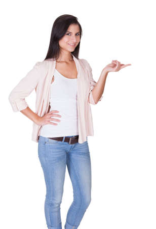 Beautiful trendy woman standing in a relaxed position with an empty palm extended in front of her isolated on white Stock Photo - 16522652
