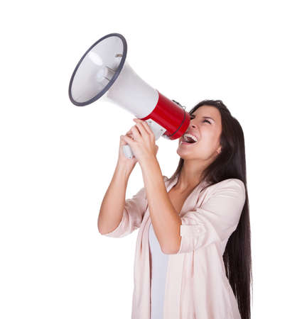 Woman holding a loud hailer above her head shouting into it with a passion isolated on white Stock Photo - 16522663