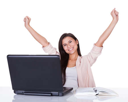 Happy beautiful vivacious female office worker or businesswoman rejoicing raising her hands high in the air Reklamní fotografie