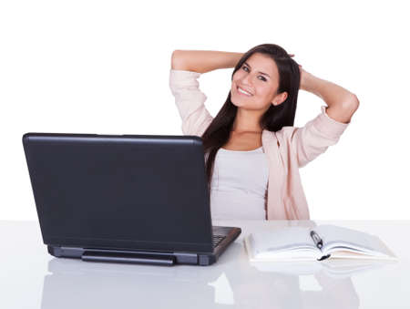 Attractive confident young professional woman sitting working at her laptop with an open book alongside her Stock Photo - 16522650