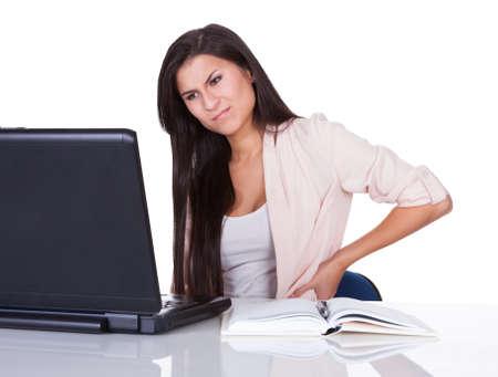 dolor espalda: Mujer con dolor de espalda despu�s de estar sentado en su escritorio en frente de su computadora port�til masajear su espalda con la mano y haciendo una mueca Foto de archivo