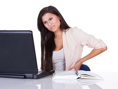 Woman with lower back pain from sitting at her desk in front of her laptop massaging her back with her hand and grimacing photo