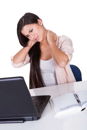 cervicales: Atractiva mujer de negocios con una rigidez en el cuello despu�s de estar sentado trabajando en su computadora port�til muecas de dolor