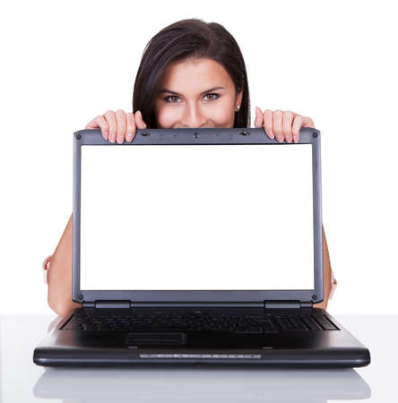 online advertising: Smiling woman with just her eyes showing standing behind a blank laptop screen with copyspace for your advertising