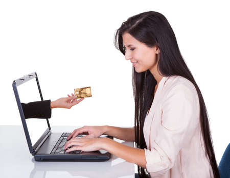detail internet computer: Woman doing online shopping or banking sitting at her laptop with a hand extending from the screen holding a credit card