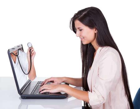 consulta médica: Mujer que mira la computadora portátil. Aislados en blanco