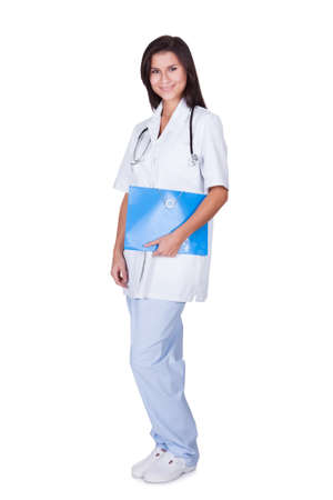 Young female doctor or nurse standing full length with a stethoscope around her neck and arms folded isolated on white Stock Photo - 16522705