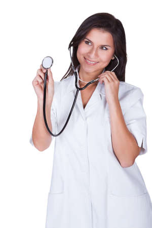 Smiling attractive female doctor or nurse holding up the disc of a stethoscope as she starts her examination isolated on white Stock Photo - 16522590