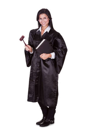 judge: Full length portrait of a female judge in a gown carrying a law book and a wooden gavel as she prepares to go to court isolated on white Stock Photo