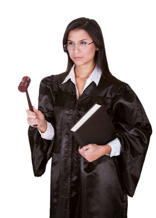 Full length portrait of a female judge in a gown carrying a law book and a wooden gavel as she prepares to go to court isolated on white photo
