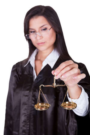 Beautiful serious female judge in a gown holding up a brass hanging scale conceptual of the Scales of Justice isolated on white photo