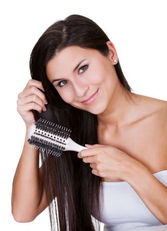 Attractive smiling woman brushing her long straight brunette hair isolated on white photo