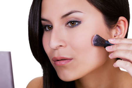 enhance: Beautiful woman applying blusher or foundation to contour and smooth the skin of her  cheek with a soft small cosmetics brush Stock Photo