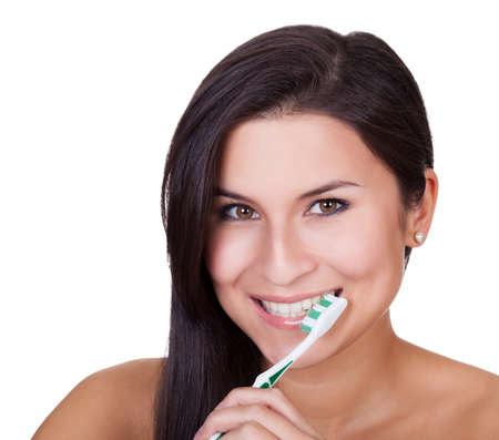 Head and shoulders portrait of a beautiful woman brushing her teeth and smiling at the camera isolated on white Stock Photo - 16522653