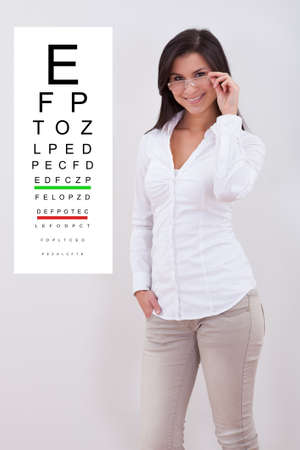 endorsement: Attractive stylish woman wearing a pair of standing next to an eye chart mounted on the wall next to her