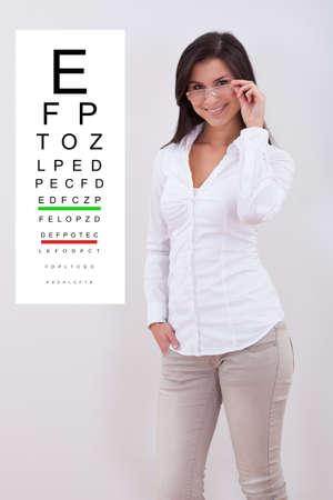 examen de la vista: Mujer atractiva con estilo con un par de pie junto a una gráfica optométrica en la pared a su lado