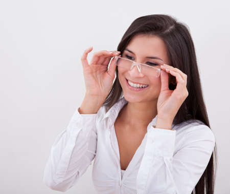 reading glasses: Happy woman wearing reading glasses with her hands raised holding the frames