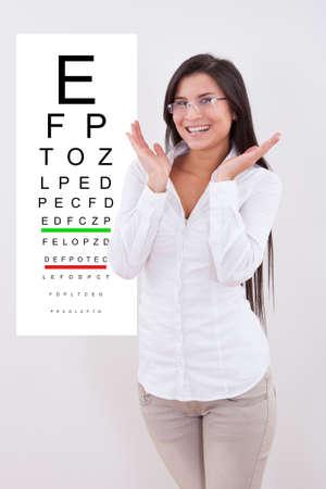 decreasing in size: Jubilant signora con gli occhiali nuovi in ??piedi davanti a un grafico di prova ottici occhio montato su una parete