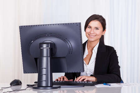 Low angle view of a relaxed smiling beautiful businesswoman sitting behind her desk working at her computer Stock Photo - 16522620