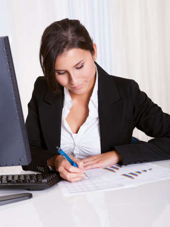 Low angle view of a relaxed smiling beautiful businesswoman sitting behind her desk working at her computer Stock Photo - 16522368