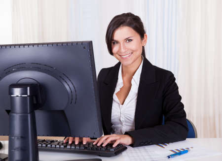 Low angle view of a relaxed smiling beautiful businesswoman sitting behind her desk working at her computer Stock Photo - 16522519