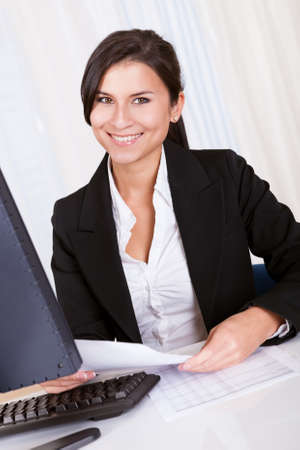 Low angle view of a relaxed smiling beautiful businesswoman sitting behind her desk working at her computer Stock Photo - 16522520